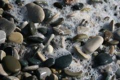 Overzees schuim op de strandkiezelstenen royalty-vrije stock foto