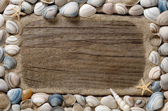 Overzees shell kader en zand op oud hout Stock Afbeelding