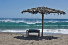 Overzees strand met de één strandbedden en de strandparaplu stock afbeeldingen
