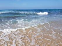 Overzees strand met kleine golven en blauwe hemel Stock Foto's