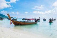 Overzees strand met kust van het de bootanker van de groeps de lange staart Stock Foto