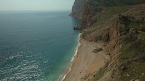 Overzees strand onder rotsen stock footage