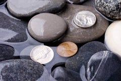 Overzees water, stenen en muntstukkenachtergrond stock foto's
