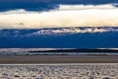Overzees water, zand, berg en wolkenlagen Stock Foto's