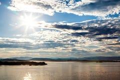Overzees, zon, hemel en bergsilhouet Royalty-vrije Stock Foto's