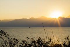Overzees, zonsondergang, bergen, wolken Stock Afbeelding