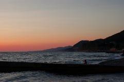 Overzees zonsondergang, strand van kiezelstenen recreatie stock foto