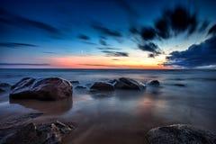 Overzees zonsondergangzeegezicht met natte rotsen Stock Afbeelding
