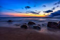 Overzees zonsondergangzeegezicht met natte rotsen Royalty-vrije Stock Foto's