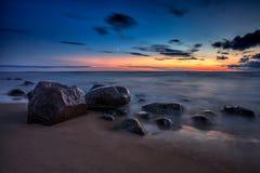 Overzees zonsondergangzeegezicht met natte rotsen Royalty-vrije Stock Afbeelding
