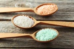 Overzees zout in houten lepels op de grijze houten achtergrond Royalty-vrije Stock Fotografie