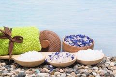 Overzees zout in lepels op kleine stenen voor een kuuroord, op een blauwe achtergrond Stock Afbeeldingen