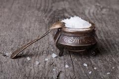 Overzees zout in oude werktuigen en een kleine lepel op een houten lijst Royalty-vrije Stock Foto's