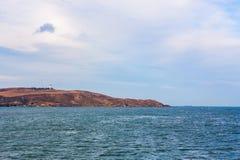 Overzeese baai op zonnige dag Bergachtige achtergrond stock fotografie