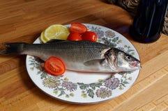 Overzeese baarzen, spigola Verse vissen met het hoofd op plaat Stock Afbeeldingen