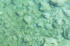 Overzeese bodem met kleine stenenkiezelstenen in glashelder water voor abstracte achtergrond Hoogste mening stock foto