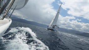 Overzeese boegzeilboot in bewolkt weer regatta Het varen regatta in de open zee stock video