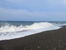 Overzeese branding en golven die op het strand verpletteren stock fotografie