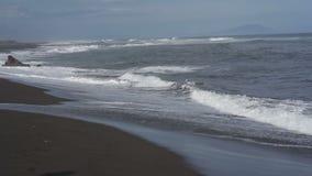 Overzeese branding op het strand met zwart vulkanisch zand in Avacha-Baai stock videobeelden