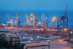Overzeese commerciële haven bij nacht in Mariupol, de Oekraïne Industriële Mening Het schip van de ladingsvracht met werkende kra stock afbeeldingen
