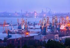 Overzeese commerciële haven bij nacht tegen werkende staalfabriek stock afbeeldingen
