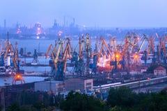Overzeese commerciële haven bij nacht tegen werkende staalfabriek royalty-vrije stock afbeeldingen