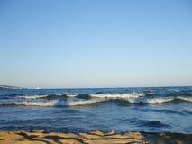 Overzeese die golven op een zandig strand worden gerold stock fotografie