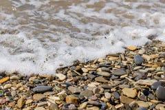 Overzeese die stenen door de golven worden gewassen stock foto