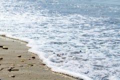 Overzeese die stenen door de golven worden gewassen stock foto's