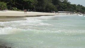Overzeese golf die op de zandige kust lopen waarop de mensen lopen Tropische zandstrand en zeewatergolf stock footage