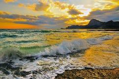 Overzeese golf op het strand, de branding op de kust van de Zwarte Zee bij zonsondergang Stock Foto's