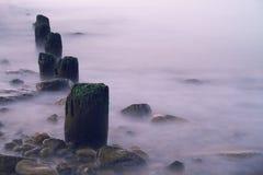 Overzeese golfbreker dichtbij strand Stock Foto