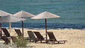 Overzeese golven die aan de kust op strand met stroparaplu's en houten sunbeds komen stock footage
