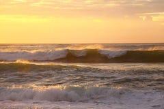 Overzeese golven die door gouden zonsopgang rollen stock afbeeldingen