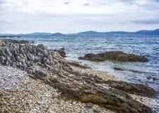 Overzeese golven die een kiezelsteenstrand en rotsen raken royalty-vrije stock foto's