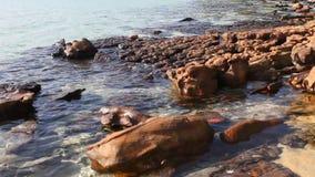 Overzeese golven die op de stenen breken stock footage