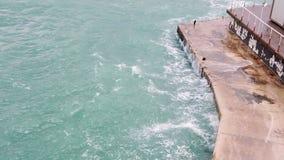 Overzeese golven die op de stenen verpletteren