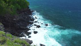 Overzeese golven die op rotsachtige klip bespatten terwijl onweer Blauwe oceaangolven die aan steenachtige kust met schuim en nev stock videobeelden