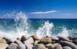 Overzeese golven die op rotsen bespatten Stock Foto
