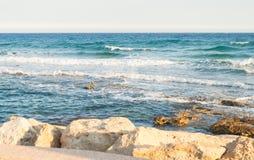 Overzeese golven die op rotsen verpletteren Golvenneerstorting stock fotografie