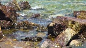 Overzeese golven die op steenachtig strand bespatten Golven die op rotsachtig strand breken Blauw zeewater en grote stenenachterg stock footage
