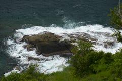 Overzeese golven die over rotsen verpletteren stock afbeeldingen