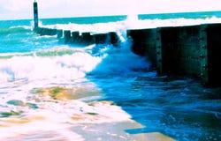 Overzeese golven die tegen een barrière verpletteren Stock Afbeelding