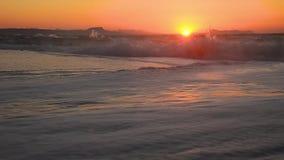 Overzeese golven op de kust bij zonsondergang stock videobeelden
