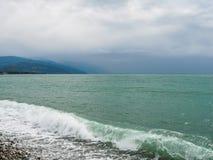 Overzeese golven op een kiezelsteenstrand stock afbeelding