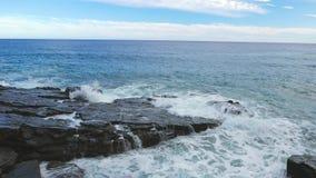 Overzeese golvenneerstorting over rotsachtige kust stock footage