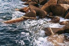 Overzeese golvenonderbreking op stenen Royalty-vrije Stock Foto's