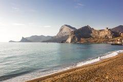 Overzeese kust en zandig strand met rotsachtige bergen op een duidelijke dag royalty-vrije stock foto