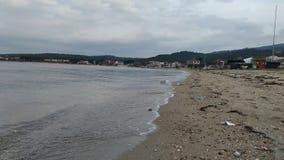 Overzeese kust op een kalme dag en een bewolkte hemel stock foto
