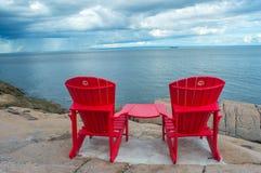 Overzeese kust Rode stoelen Stock Fotografie